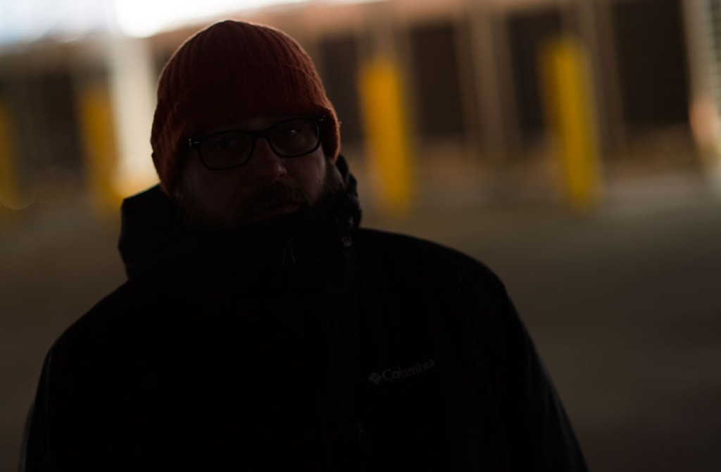 Nikon D4s, 100ISO, Nikon 85mmF1.4D, 1/800th@F2. Phottix Mitros+ speedlight on the ground in the parking garage about 50' behind the subject aimed at the generators in the background Speedlight both triggered and set to 1/1 power by a Phottix ODIN transmitter on the camera hot shoe